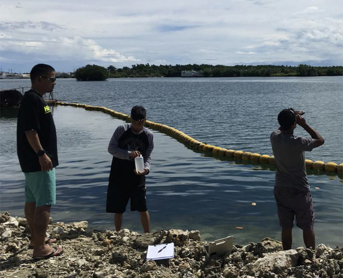 Three students stand on shoreline, one holding a water sample bottle