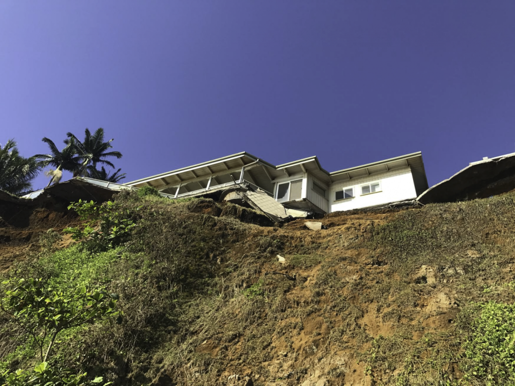 A home precariously near an eroding sea cliff with some damage to the back patio where it looks like some parts of the structure has fallen.