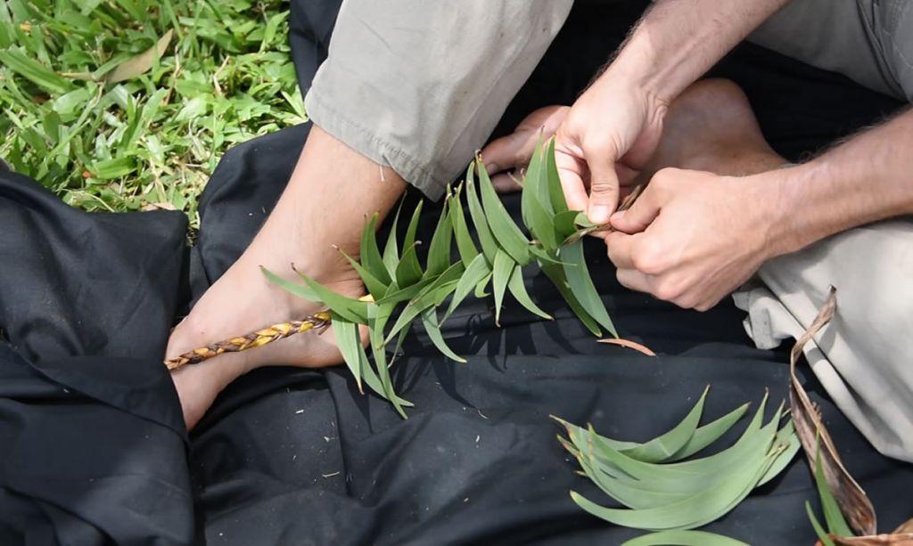Person weaving a haku lei with koa leaves and ti leaf.