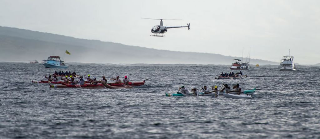 Several canoes and teams racing in ocean with support boats and helicopter surrounding.