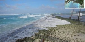 Ocean water runs several feet across low-lying cement barrier and sand of island