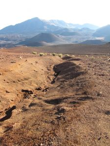 An eroded gully stretches along an open plain to cinder cones in the background