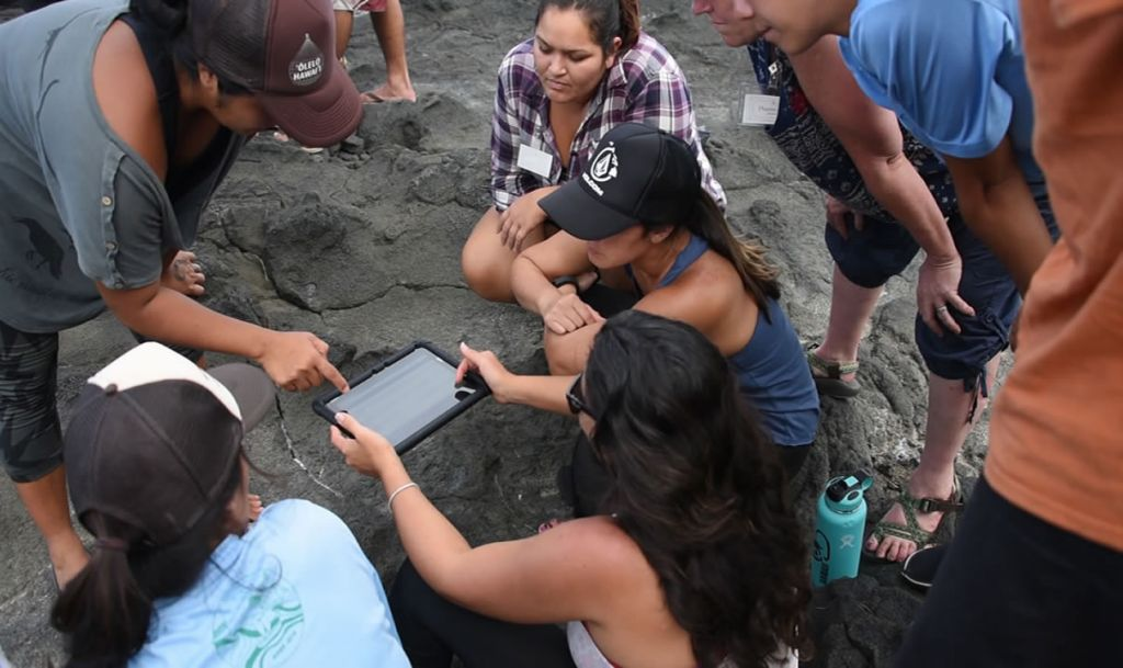 Group of participants on rocky shoreline gathered around tablet and learning.