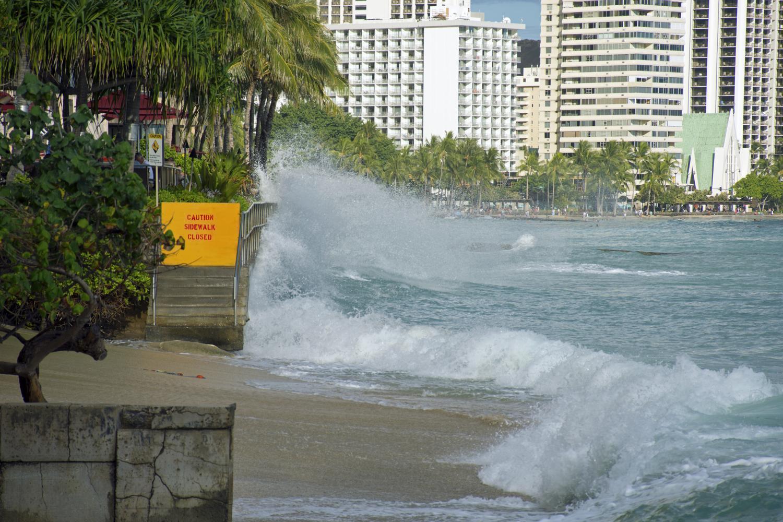 "Waves splash against a railed cement wall that bears a ""Caution: Sidewalk closed"" sign."