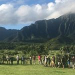 People arranged in a circle with background of mountains of the Pali