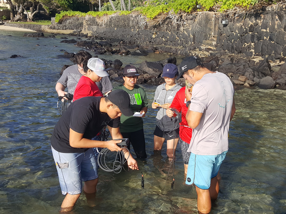 Students taking water measurements while standing in a stream