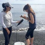 A professor reads off an instrument while her student records information, on the blacksand shore of the bay.