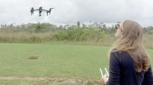 A student controls a drone rising above a grassy field.