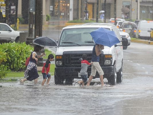 A family wades across a flooded road in Tumon, Guam