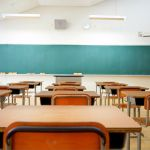Empty desks face a blackboard in a classroom