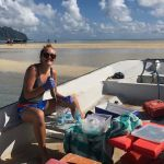 A student, grinning at the camera, sits in a small boat beached on a sandbar while she takes water samples from a bag