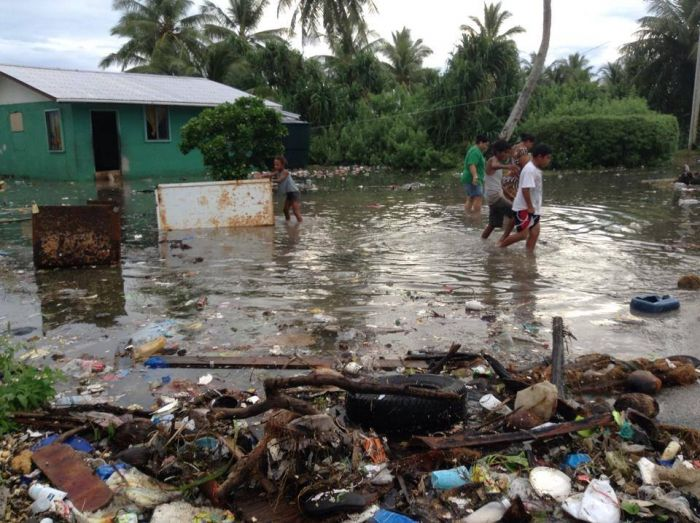 Local children wade through calf-high dirty water, past flood accumulated trash and a flooded house.