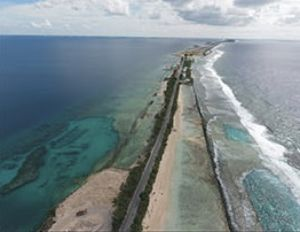 A thin strip of land with a straight two-lane road retreats into the distance with ocean on either side.