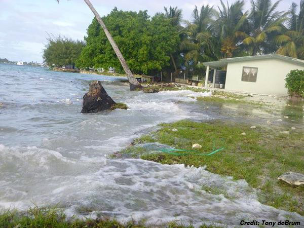 Ocean water floods over a lawn and into a house along a low shoreline.