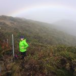 A student stands near a fence on a scrub-covered hillside with a faint rainbow in the mist behind her.