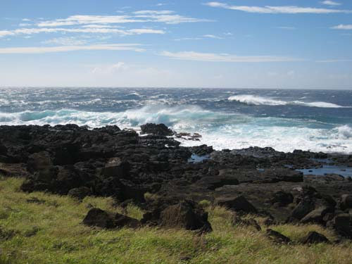 Wind-swept waves tumble towards a rocky shoreline.