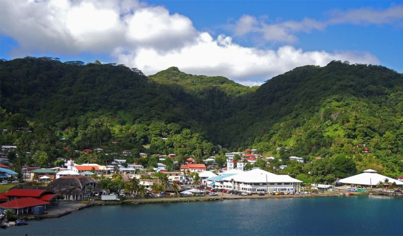 Scenic view of low-lying buildings nestled between the base of tree-covered slopes and a blue bay.