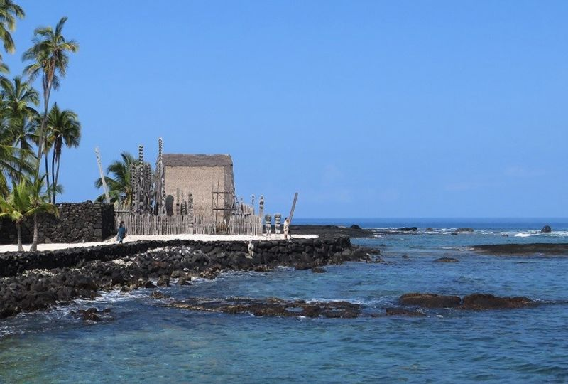 A small historical hut backed by palms sits on a rocky headland with waves in the foreground.