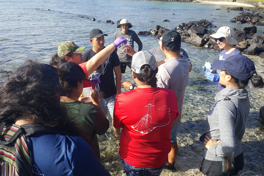 A group of college students on the shore all look to one holding a water sample.