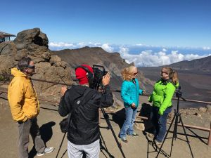 A cameraman focuses on host and scientist overlooking Hawaiian landscape