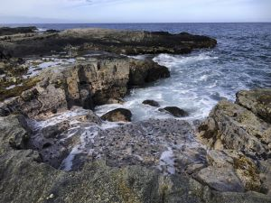 Levels of rocky outcrops show shades of color, dropping off to the churning ocean.