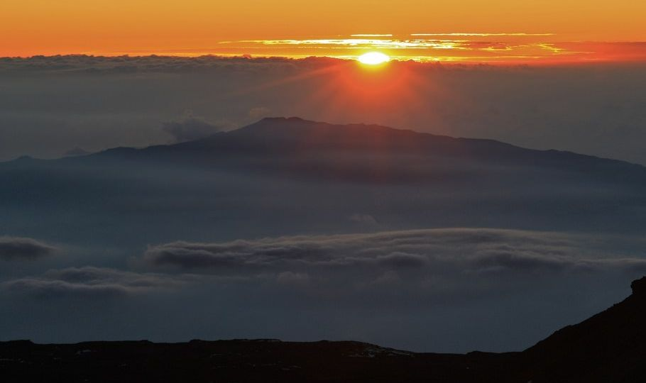 A glowing sun sinks behind a cloudbank with mountains peeking out of the cloud layer in the midground.