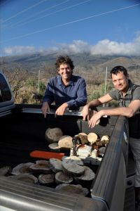 Patrick Hart poses with a collaborator next to a truck with cut slices of tree trunks.