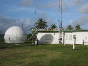 An exterior shot shows satellite and radar dishes and a radio tower outside a low building.