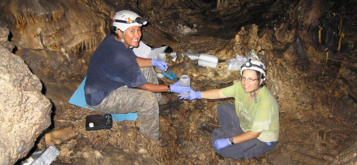 Two students in hardhats smile at the camera while seated on the floor of a cave, with water sampling gear around them.