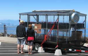 A two-level greenhouse on wheels sits in a parking lot for visitors to look at.