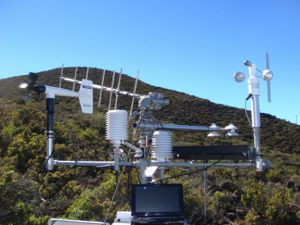 A complex of atmospheric instruments sit together on a boom placed in the midst of a shrubby landscape.