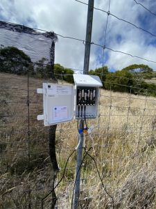 A wired box is attached to a metal pole that is part of a wire fence in a dry grassy fields.
