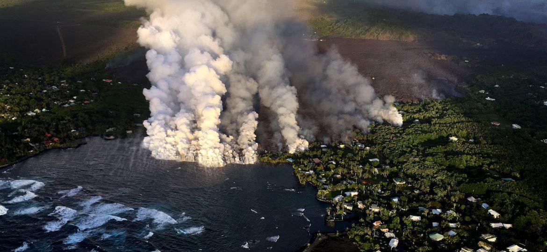 Aerial image of lava flow entering Kapoho Bay displaying lots of smoke billowing.