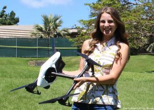 Rose Hart holding an unmanned aerial vehicle in a field.