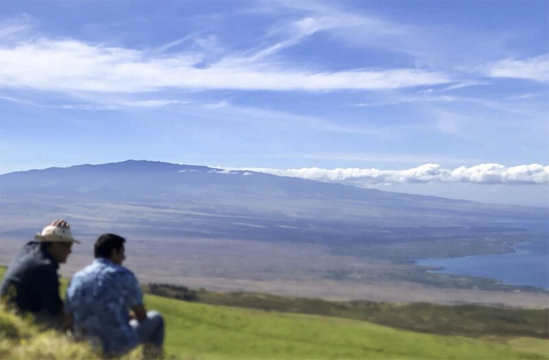 Two people in the foreground sitting in a grassy field look out over landscape toward the coast and Hualalai Volcano