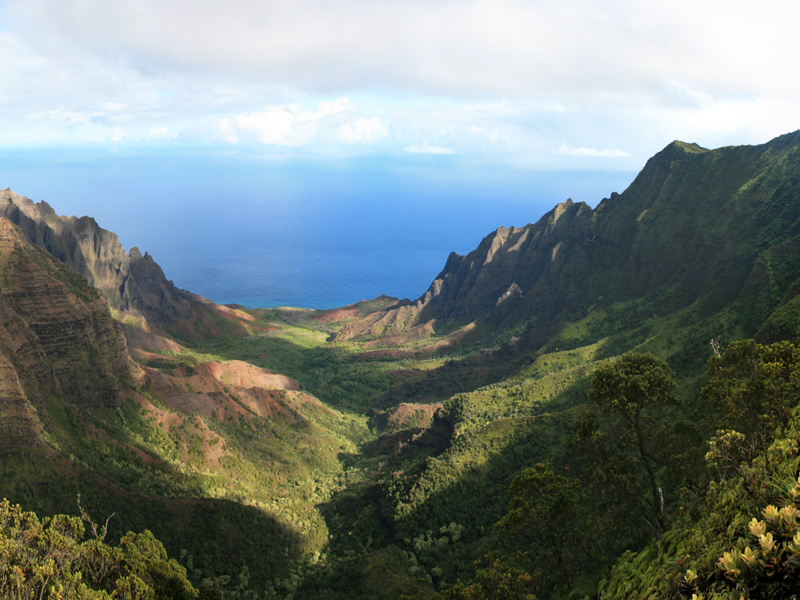 View from the top of a steep, green-sided, u-shaped valley opening onto a blue ocean