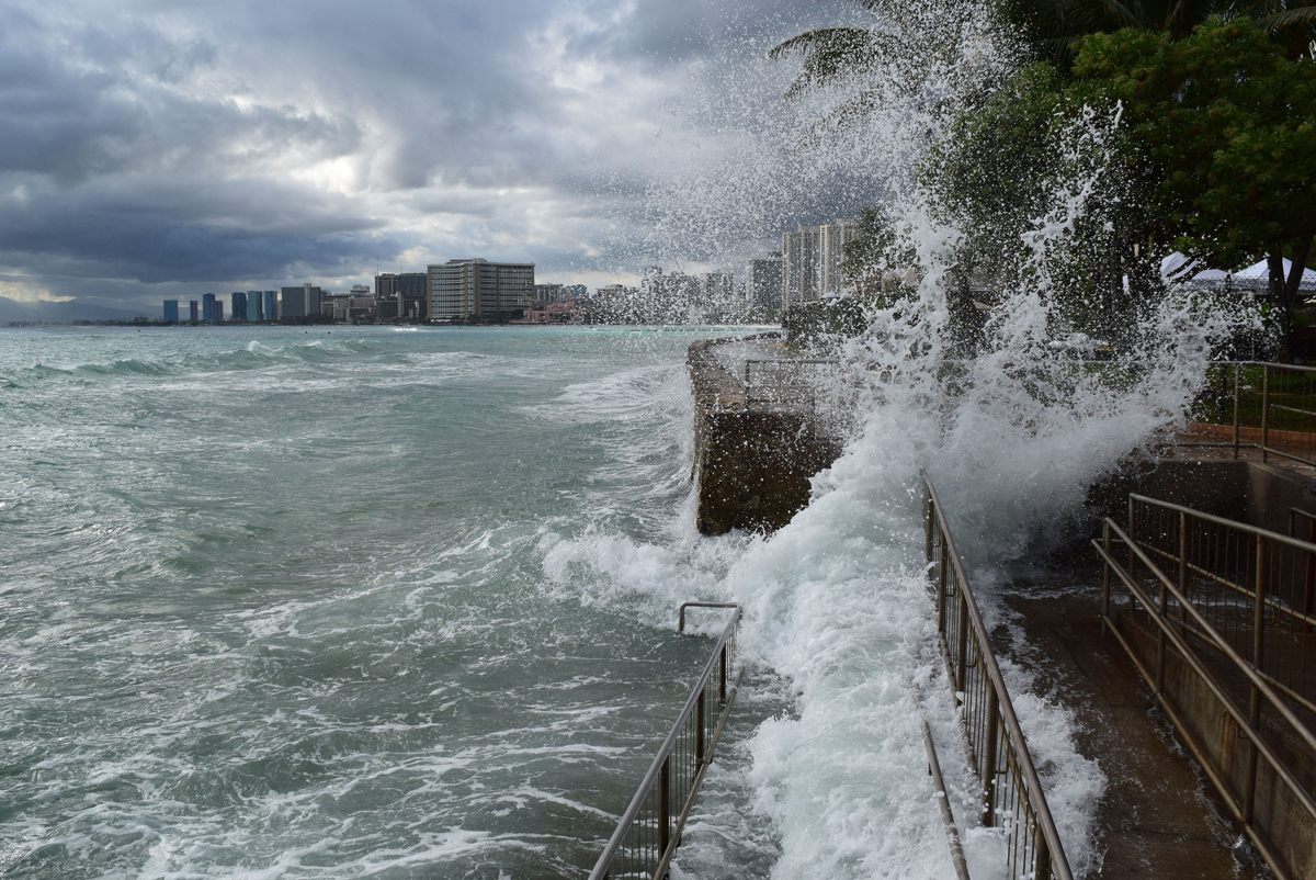 A wave crashed up and over a railed walkway in Waikiki